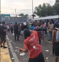 central american migrants riot on the border bridge with Mexico